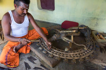 KUMBAKONAM, INDIA - OCTOBER 11, 2013: Sitting man corrects and cleans impurities with hand tools of large metal statue that came out of the cast.