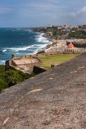 ramparts: SAN JUAN, PUERTO RICO - MARCH 14, 2015: View from the ramparts of Castillo San Felipe del Morro to the east: the Atlantic Ocean, Part of ramparts, Cemetery Santa Maria Magdalena, La Perla bario and beyond under a blue sky.