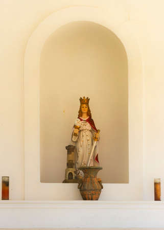 identifies: SAN JUAN, PUERTO RICO - MARCH 6, 2015: Castillo San Christobal. The statue of Santa Barbara in the chapel, devoted to her, at the Castillo. The tower on her side identifies her.