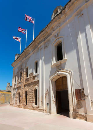 SAN JUAN, PUERTO RICO - MARCH 6, 2015: Castillo San Christobal. Facade of the palace. Three flags fly above the palace: the US flag, the Puerto Rico flag and the Cross of Burgundy, a Spanish military flag used between 16th and 18th century. Editorial
