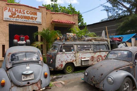 trashed: SAN JUAN, PUERTO RICO - MARCH 13, 2015: Junk yard adjacent to a coin laundry business in Tras Talleres neighborhood holds trashed, old, gray Volkswagen cars and van. Other stuff lies around unde blue sky. Editorial