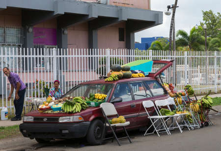 SAN JUAN, PUERTO RICO - MARCH 13, 2015: Farmer and wife sell fruit and vegetables illegally out of their Toyota car in the street of Tras Talleres neighborhood. Editorial