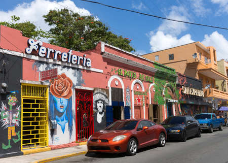 blue facades sky: SAN JUAN, PUERTO RICO - MARCH 13, 2015: Facades of bars and restaurants in Calle Elisa Colberg in the Tras Talleres neighborhood. Parked cars, wall paintings and graffiti. Blue sky with white clouds.