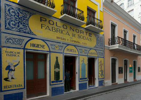figurative: SAN JUAN, PUERTO RICO - MARCH 13, 2015: The historic colorfully tiled facade of an old soda maker business in Old San Juan. Figurative and non figurative images. Yellow and blues are dominant.