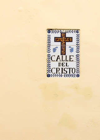 identifies: SAN JUAN, PUERTO RICO - MARCH 14, 2015: Historic, tiled sign identifies the street and shows the symbol of a cross. The wall is pale yellow, as banana flesh.