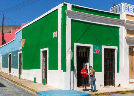 SAN JUAN, PUERTO RICO - MARCH 6, 2015: A corner pub has been painted completely in the Heineken green. The red Heineken star is the only thing that gives the name away. Two patrons negotiate a deal in front. Blue sky. Editorial