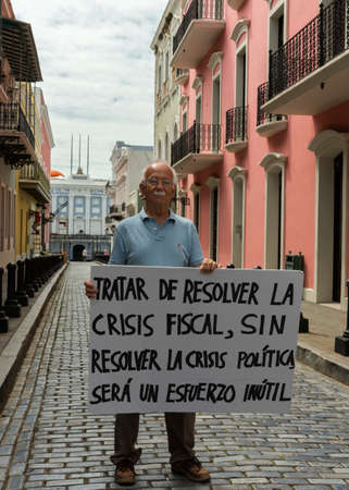 activist: SAN JUAN, PUERTO RICO - MARCH 8, 2015: Lone nationalist political activist addresses the Governor. He holds a sign that reads: trying to solve the fiscal crisis without first solving the political crisis is a waste of time. The older man stands alone in t