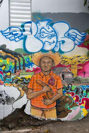 graffiti brown: SAN JUAN, PUERTO RICO - 07 de marzo 2015: Graffiti en el barrio de la Universidad. Imagen colorida muy aguda de un hombre joven, de color marr�n en camisa naranja rodeado de desastres ambientales, como la industria, la destrucci�n barrio, explosiones nucleares. Se�ala Editorial