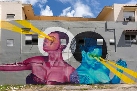 SAN JUAN, PUERTO RICO - MARCH 13, 2015: Graffiti in Tras Talleres neighborhood. Very sharp colorful image of the torsos of a pink woman and an azure woman, both beaming light out of their eyes. It seems they are dancing. Gray back wall. Editorial