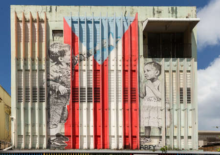 SAN JUAN, PUERTO RICO - MARCH 13, 2015: Graffiti in Tras Talleres neighborhood. Large image of a Caucasian boy and an African girl adding the star to the Puerto Rico Flag. Painted on a tall, white warehouse wall. Both children are painted in black and whi