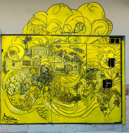SAN JUAN, PUERTO RICO - MARCH 13, 2015: Graffiti in Tras Talleres neighborhood. Very sharp image of only black drawing on solid lemon-yellow painted garage door. Subject is a tropical, bucolic garden scenery with two suns and one moon. Editöryel