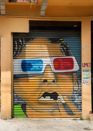expressed: SAN JUAN, PUERTO RICO - MARCH 13, 2015: Graffiti in Tras Talleres neighborhood. Very sharp image of brown face wearing the red and blue 3D glasses. Surprise expressed on the face. A satellite, named Gaza, reflected in one glass. Painted on a peach colored
