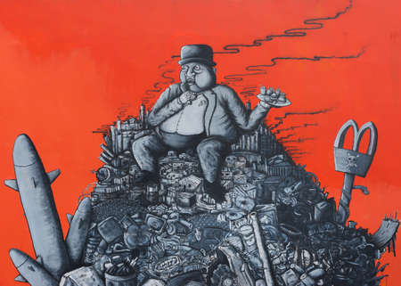corporate waste: SAN JUAN, PUERTO RICO - MARCH 13, 2015: Graffiti in Tras Talleres neighborhood. Very sharp image of fat capitalist, banker, sitting on a heap of corporate junk such as logos, bombs, smoke stacks, skulls and waste. Drawn in black on blood red wall.