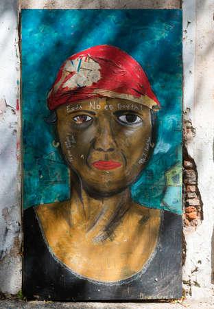 graffiti brown: SAN JUAN, PUERTO RICO - 06 de marzo 2015: Graffiti en el barrio de Viejo San Juan. Muy fuerte imagen del torso de una mujer que mira seriamente marr�n con un pa�uelo rojo y los labios de color rojo brillante sobre un fondo azul. Un texto writen sobre la imagen lee: ella no es