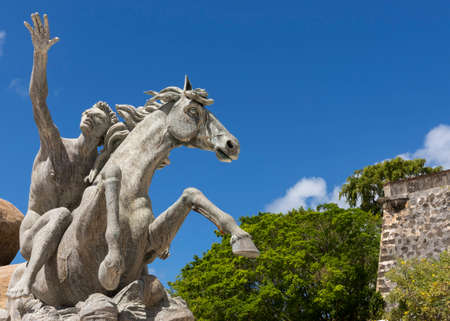 SAN JUAN, PUERTO RICO - MARCH 8, 2015: The Raices Fountain, celebrating the diversity of the population, stands dry under a blue sky. Detail of statue: man on horse with city wall and trees as background.