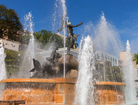 SAN JUAN, PUERTO RICO - MARCH 13, 2015: The Raices Fountain, celebrating the diversity of the population, jets water under a blue sky. Detail of statue: the woman in triumph, and the woman riding dolphins. Stock Photo
