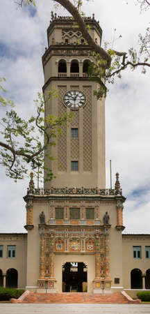 SAN JUAN, PUERTO RICO - MARCH 7, 2015: The Roosevelt Bell Tower at the University of Puerto Rico in all its glory. Seen from under a tree. Monumental gate at the bottom in full view. Under cloudy sky with a couple of blue patches.