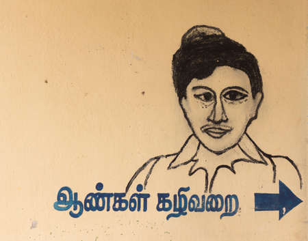 KUMBAKONAM, INDIA - OCTOBER 12, 2013: Sign for Mens toilet with explanation in Tamil language. Primitive drawing of the head of a man with splint eyes on a beige background. Editöryel