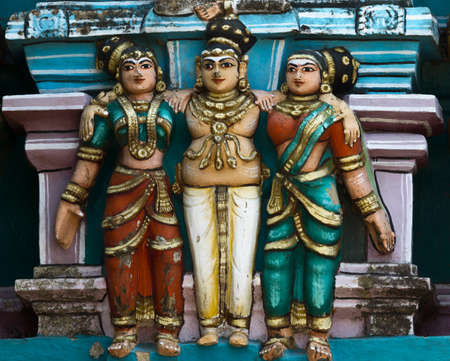 black mold: KUMBAKONAM, INDIA - OCTOBER 12, 2013: Mahalingeswarar Temple. Wear and tear have damaged the lesser Gopurams. Cute trio statue of a male and two females on top of said Gopurams. Black mold affected the pastel colors. Editorial
