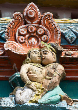 black mold: KUMBAKONAM, INDIA - OCTOBER 12, 2013: Mahalingeswarar Temple. Wear and tear have damaged the lesser Gopurams. Cute statue of kissing couple. A twig of a fresh grown tree peeps between their faces. Black mold affected the pastel colors.
