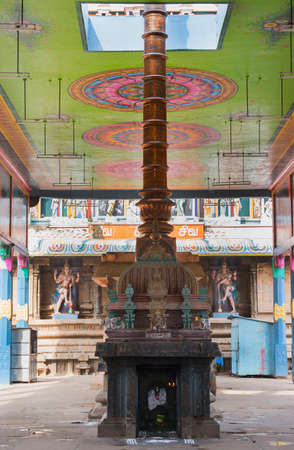 parvati: KUMBAKONAM, INDIA - OCTOBER 12, 2013: Mahalingeswarar Temple. An open-sided hall or walkway leads to the inner sanctum. The tall, copper flagpole reaches through the painted ceiling. A blackened Ganesha shrine fronts it. Two Dwarapalakas, door keepers of  Editorial