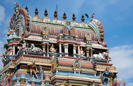 KUMBAKONAM, INDIA - OCTOBER 12, 2013: Mahalingeswarar Temple. The top of the Gopuram shows plenty of Hindu religious statues and symbols. Nandi present so is Lord Shiva himself on the short left side. Plenty of pastel colors against a blue sky. Editorial
