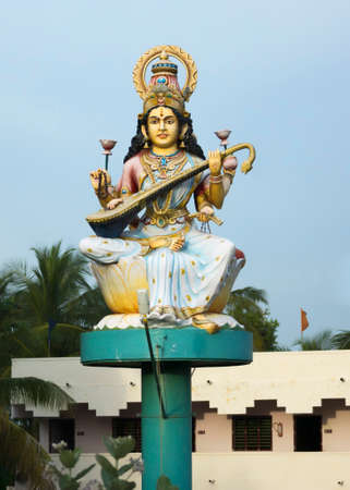 KUMBAKONAM, INDIA - OCTOBER 12, 2013: The goddess Saraswathi sits on a circular platform fixed on a single pole. Statue in front of school along the rural road against a light blue sky. She's the goddess of education and plays the Veena instrument.
