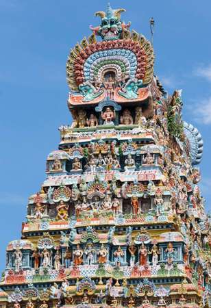 disciples: KUMBAKONAM, INDIA - OCTOBER 12, 2013: Mahalingeswarar Temple. Tower is verloaded with tens of pastel colored statues of deities and others. The central statue of Lord Shiva with a few disciples and his foot on the dwarf is Him in his Dhaksinamurthy avatar