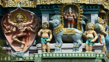 parvati: KUMBAKONAM, INDIA - OCTOBER 12, 2013: Mahalingeswarar Temple. Statue composition on Gopuram. The figure on the left is Lord Shiva, the slayer of the elephant, who skinned the animal and wore the skin as a garment. The figure on the right is Lord Ganesha s Editorial