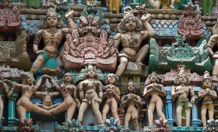 KUMBAKONAM, INDIA - OCTOBER 12, 2013: Sarangapani Vishnu Temple. Focus on Naked, pastel colored statues of a group of naked women and men. Two Dwarapalakas, door keepers, stand guard above. A small selection of the plus hundred figurines on the tower. Wea