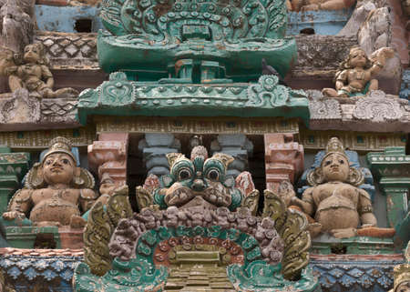 black mold: KUMBAKONAM, INDIA - OCTOBER 12, 2013: Sarangapani Vishnu Temple. Focus on two Dwarapalakas, gate keepers, protectors of the temple. A small selection of the plus hundred figurines on the tower. Weather wear and tear have damaged the statues. Black mold is
