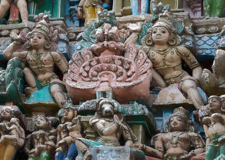 vishnu: KUMBAKONAM, INDIA - OCTOBER 12, 2013: Sarangapani Vishnu Temple, entrance Gopuram statues. Sampler of smaller statues around two larger Dwarapalaka statues. A small selection of the plus hundred figurines on the tower. Weather wear and tear have damaged t Editorial