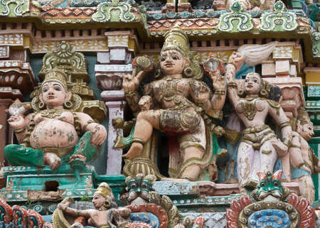 KUMBAKONAM, INDIA - OCTOBER 12, 2013: Sarangapani Vishnu Temple, entrance Gopuram statues. One Dwarapalaka with a sitting and a waiving servant. A small selection of the plus hundred figurines on the tower. Weather wear and tear have damaged the statues.  Editorial