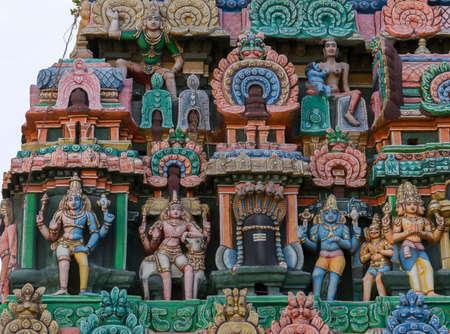 KUMBAKONAM, INDIA - OCTOBER 13, 2013: Kumbeswarar Temple Gopuram. Triumvirate of Hindu gods in the same photo: Shiva, Vishnu, Brahma. Krishna as baby breastfed by Putana. From the left: one person is the pale Shiva and the blue Vishnu. Shiva leaning on Na Editorial