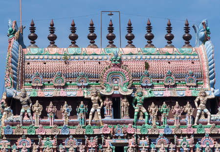 parvati: KUMBAKONAM, INDIA - OCTOBER 13, 2013: The Kumbam, the apex on top of the Kumbeswarar temple Gopuram shows a row of pastel colored statues. The bigger images are Dwarapalakas, gate keepers.