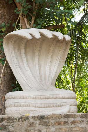 Kumbakonam, Indien - 13. Oktober 2013: Eine kleine Straße seitigen Schrein eines großen, weißen fünfköpfige Kobra Statue. Shesha ist der König der Nagas und einer der Ur-Wesen der Schöpfung. Shesha lobte Vishnu. Standard-Bild - 42008427