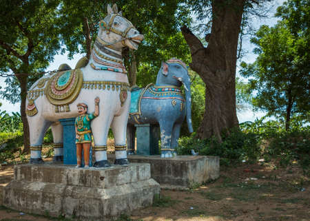 supposed: THANJAVUR, INDIA - OCTOBER 13, 2013: Road-side, colorful statues of horse and elephant at the approach of a village. Both animals are supposed to protect the village and its inhabitants from evil.