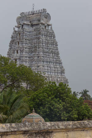 Trichy, India - October 15, 2013: The dirty-white, Vellai Gopuram at the Sri Ranganathar Swamy sanctuary, towers over green trees against a rain-filled, gray sky. Editorial
