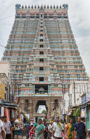 perimeter: Trichy, India - October 15, 2013: Frontal view on the massive Rajagopuram of Ranganathar Temple. View from street leading to the tower inside the temple perimeter. Plenty of people and small shops in the picture.
