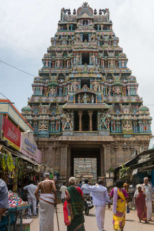 Trichy, India - October 15, 2013: One of the shorter gopurams near inner circle of Ranganathar Temple. Facade is set with statues. Pastel colors galore. People walking to gopuram.