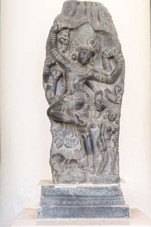 nataraja: Thanjavur, India - October 14, 2013: Cholas era statue of the dancing Lord Shiva at the Thanjavur Palace. Hard granite placed against white wall. This pose of Shiva is called Nataraja. Parts of his body have been blackened by numerous caresses of the fait