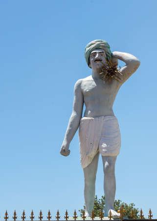 obrero: Thanjavur, India - 14 de octubre de 2013: Estatua del trabajador común, el hombre de bigotes que trabaja en los campos de arroz. hombre blanquecino contra el cielo azul. Lleva un turbante verde, un dhoti y tiene paja falsa en el hombro. Editorial