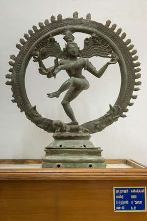 nataraja: Thanjavur, India - October 14, 2013: Cholas era statue of dancing Lord Shiva in Nataraja pose at the Thanjavur Palace. He is captured in a see-through wheel. Hard granite placed against white wall.