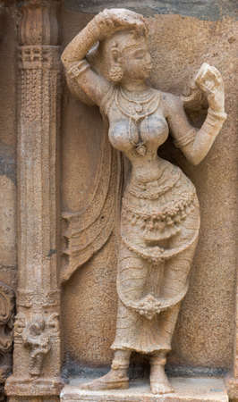 narcissism: Trichy, India - October 15, 2013: Sandstone statue of woman looking at herself in handheld mirror at Ranganathar Temple. Outside wall of old part built during Madurai Nayak era. Editorial