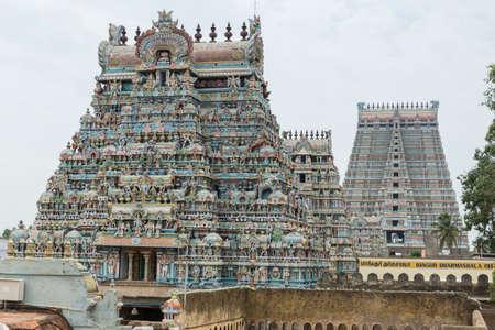 Trichy, India - 15 oktober 2013: Schot van het dak van dubbele entree Gopurams plus de zeer hoge Rajagopuram op de achtergrond. Overvloed van pastel standbeelden en zilver luchten.