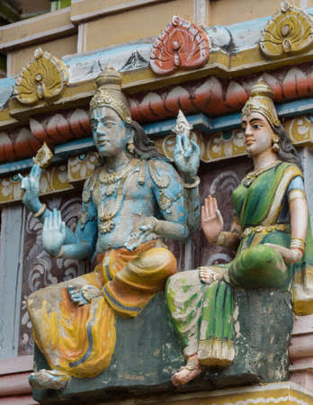 vishnu: Trichy, India - October 15, 2013: Detail of facade of short Vimanam at Ranganathar Temple. Tower stands on top of old part built during Madurai Nayak era. Statue of Lord Vishnu and his wife. He holds his discuss and conch. Editorial