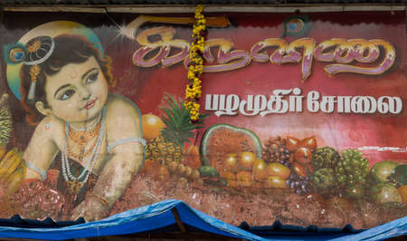 Trichy, India - October 15, 2013: Billboard on which Lord Krishna promotes the business of a fruit vendor in the streets near Shirangam Temple. Toddler playing among pineapple, tomatoes, grapes and more.