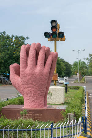 monument in india: Trichy, India - October 15, 2013: Solidarity and cooperation monument along main boulevard of the city. Two large pink hands joining together with traffic lights as background.
