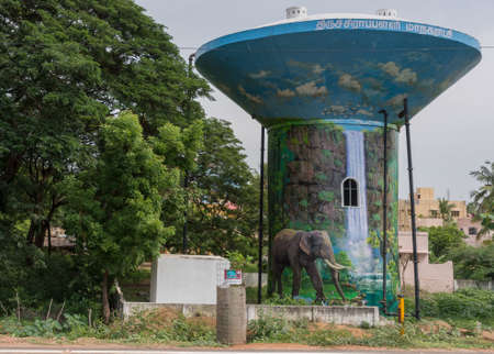 Trichy, India - October 15, 2013: Tall water tower is painted with a jungle theme showing a water fall and an elephant, all against blue background. The tower stands besides green trees. Editorial