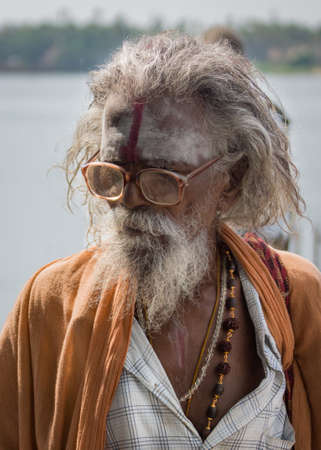 garb: Trichy, India - October 15, 2013: Old, graying sadhu with beard and glasses. Wears orange garb and has his forehead smeared with white and red. Seen in Anna Mandapam. Editorial